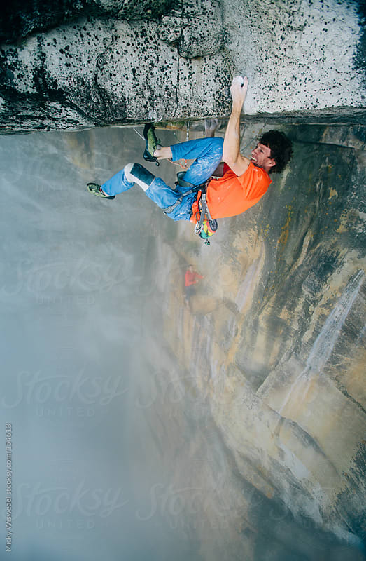 Rock climber/mountaineer climbing an extreme overhanging roof on table mountain by Micky Wiswedel for Stocksy United