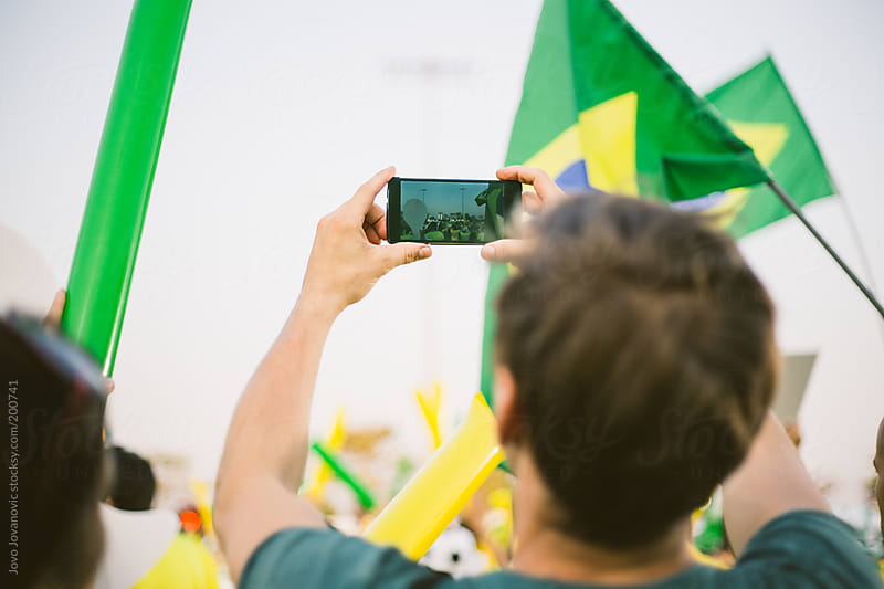 Football fan watching game and capturing moment with his smart phone by Jovo Jovanovic for Stocksy United