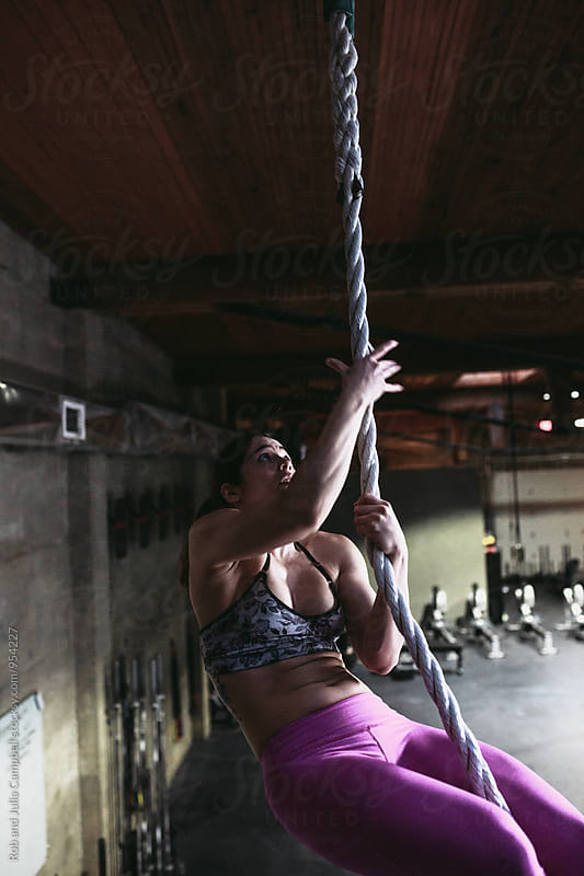 Active, fit mixed race woman training hard with ropes in workout gym by Rob and Julia Campbell for Stocksy United