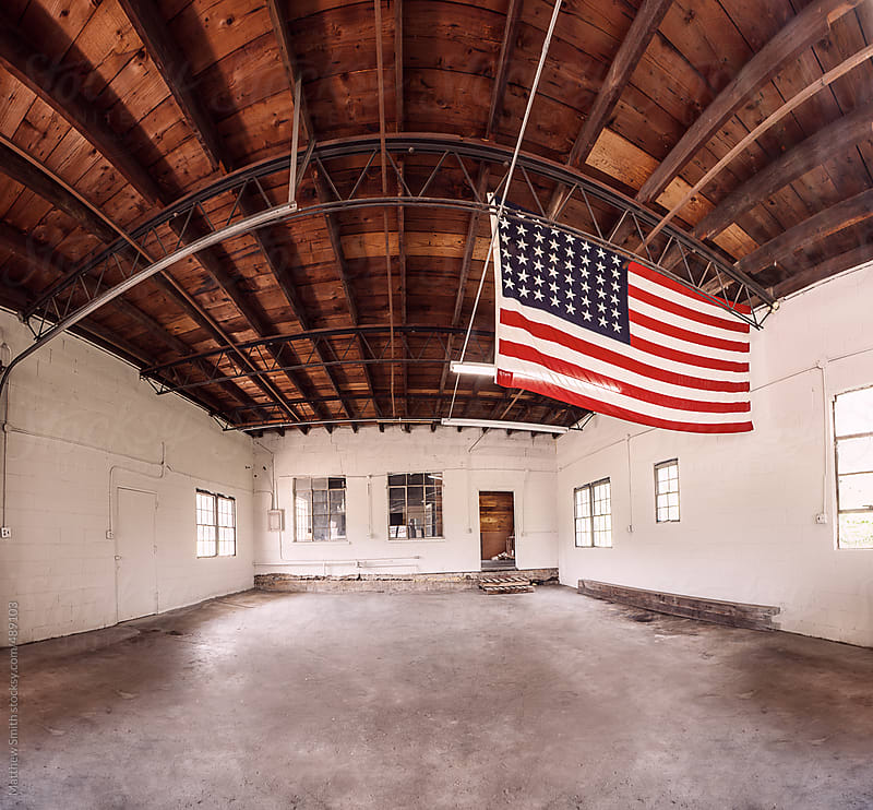 An Empty Building With An American Flag Hanging From The Ceiling. by Matthew Smith for Stocksy United