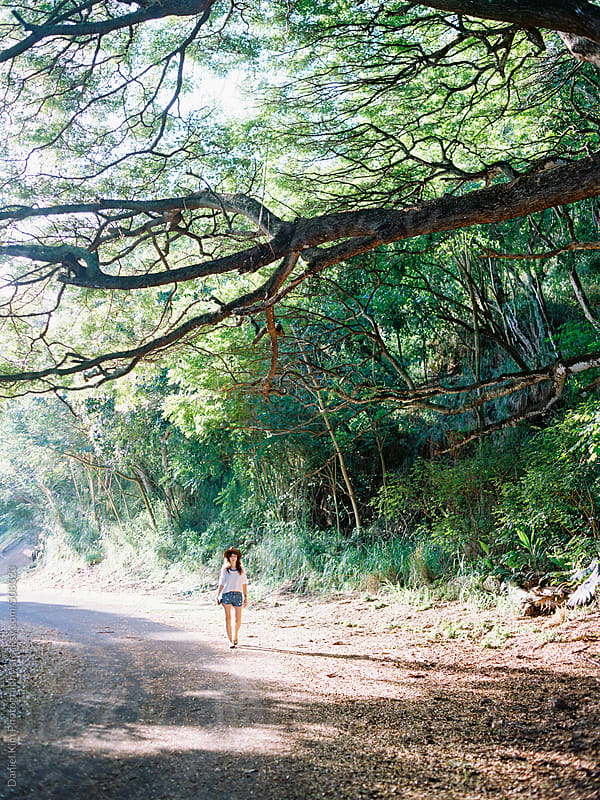 Woman walking in tropical forest by Daniel Kim Photography for Stocksy United