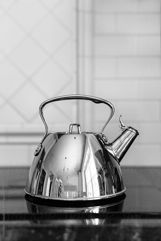 Shiny tea kettle on stove top by Matthew Spaulding for Stocksy United
