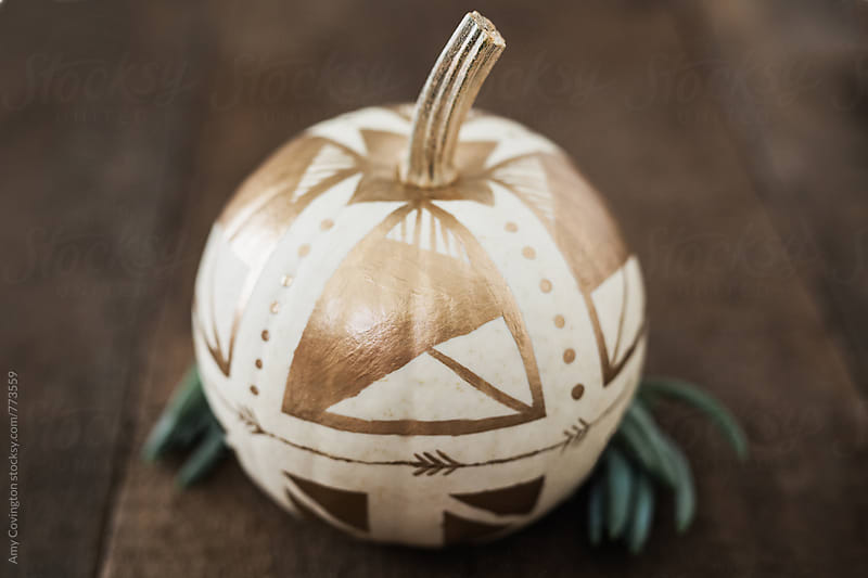 A white pumpkin painted with gold paint by Amy Covington for Stocksy United