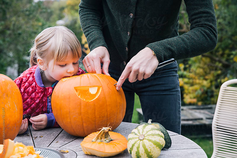 Mother and daughter carving pumpkin for Halloween by Lior + Lone for Stocksy United