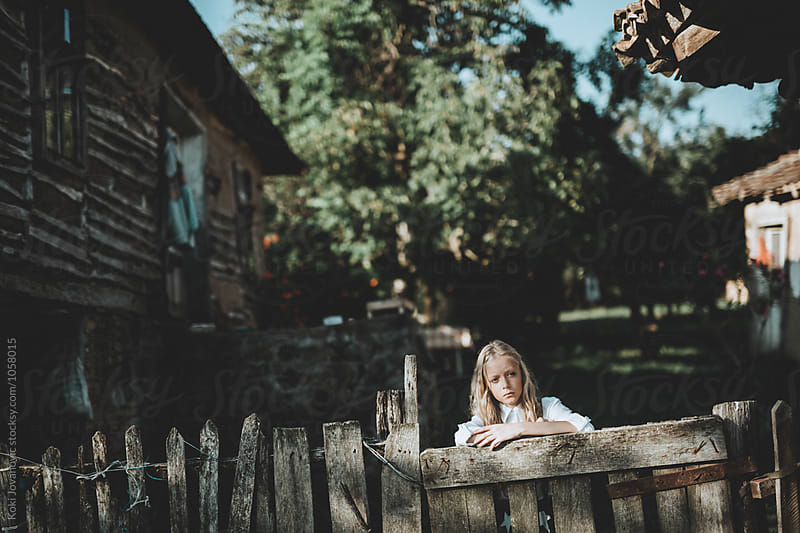 Little Girl In Front Of old House by Koki Jovanovic for Stocksy United