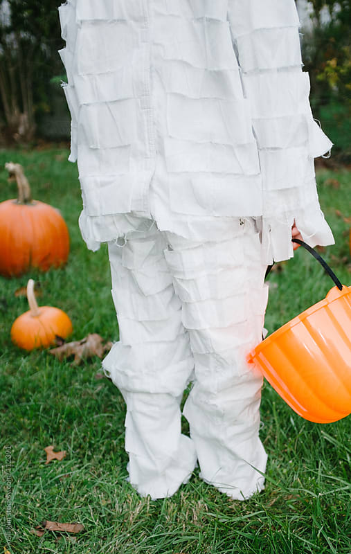 Rear View Of Child Dressed In Mummy Costume Holding Pumpkin Basket by kelli kim for Stocksy United