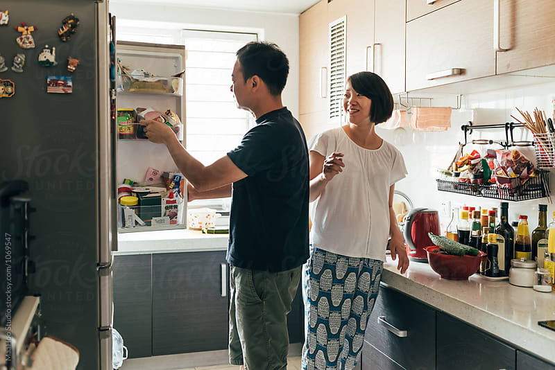 Pregnant woman and her husband at kitchen by MaaHoo Studio for Stocksy United