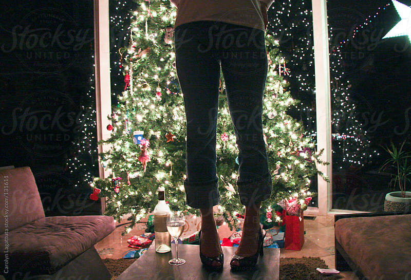 Woman standing on a table in front of the Christmas tree with a bottle of wine at her feet by Carolyn Lagattuta for Stocksy United