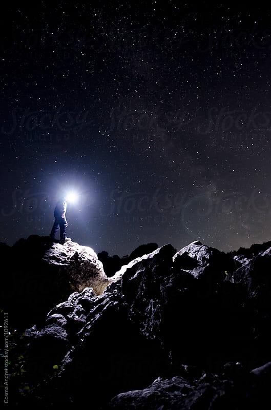 Man under stars exploring mountain by Cosma Andrei for Stocksy United