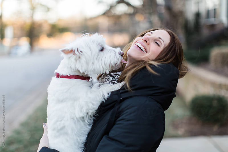 A cute dog and an attractive woman showing affection on a sidewalk by Jakob for Stocksy United