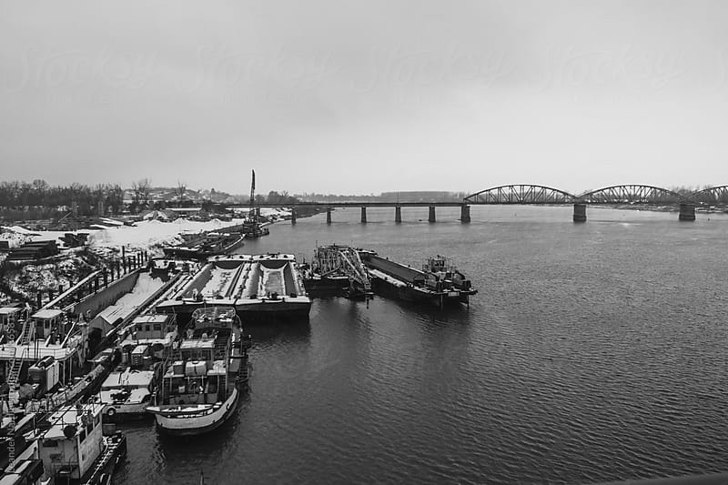 rail bridge above the danube river in belgrade with old boats on the shore - black and white by Leander Nardin for Stocksy United