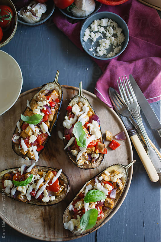 Roasted aubergine stuffed with spiced vegetables and cheese on a table. by Darren Muir for Stocksy United