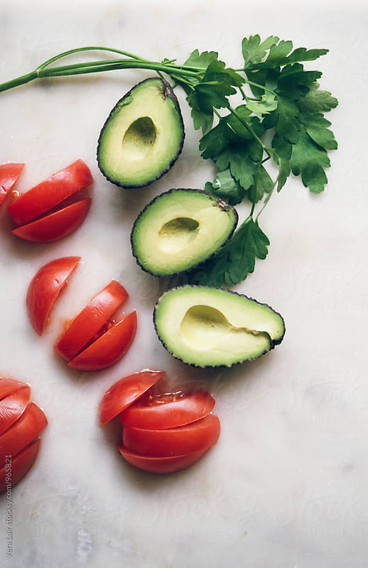 Small avocados and tomatoes by Vera Lair for Stocksy United