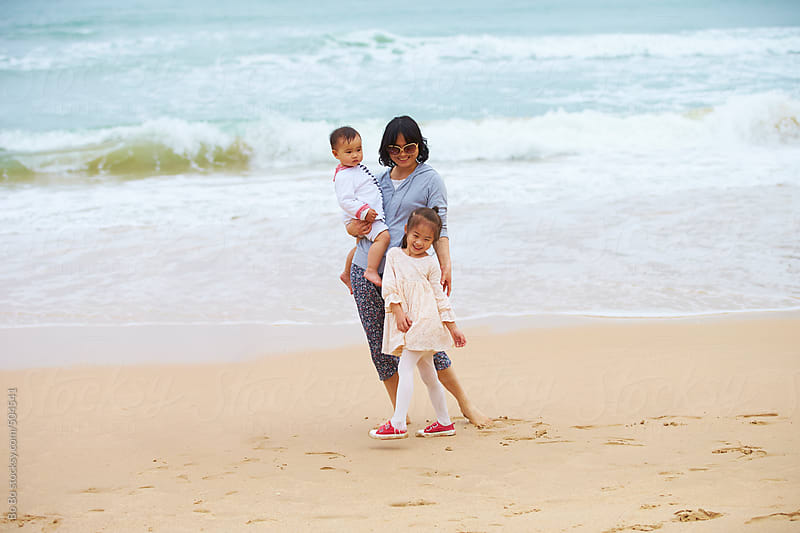 happy young asian mother with her kid on beach by Bo Bo for Stocksy United