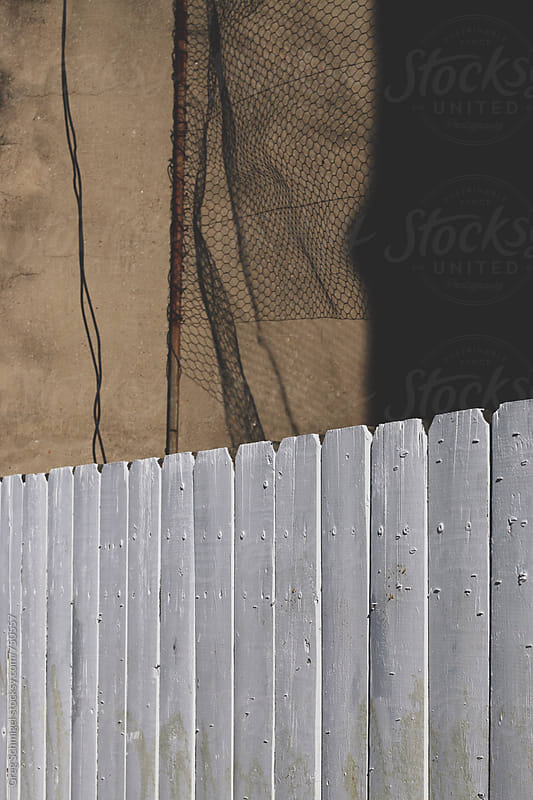 A white fence with shadows and light on a concrete wall by Greg Schmigel for Stocksy United