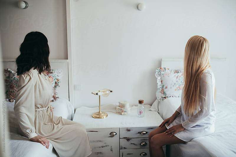 Two fashionable young women sitting on the bed by Jovana Rikalo for Stocksy United