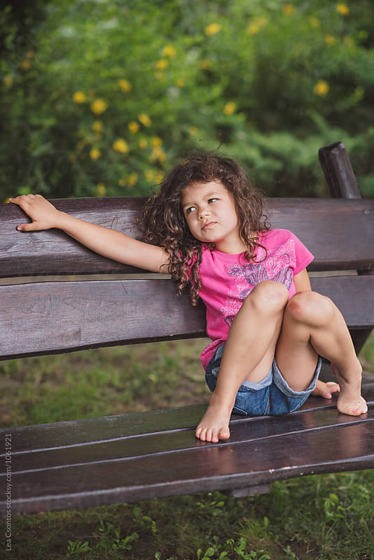 Sulky little girl sitting on a bench by Lea Csontos for Stocksy United
