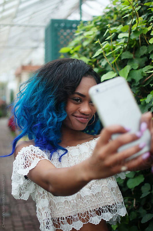 A young woman taking a self portrait with a mobile cell phone by Chelsea Victoria for Stocksy United