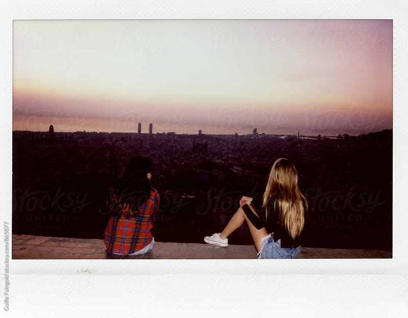 Back view of two female friends enjoying cityscape by Guille Faingold for Stocksy United
