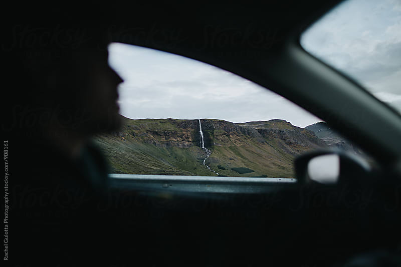 Man Driving Car Past Scenic Landscape in Iceland by Rachel Gulotta Photography for Stocksy United