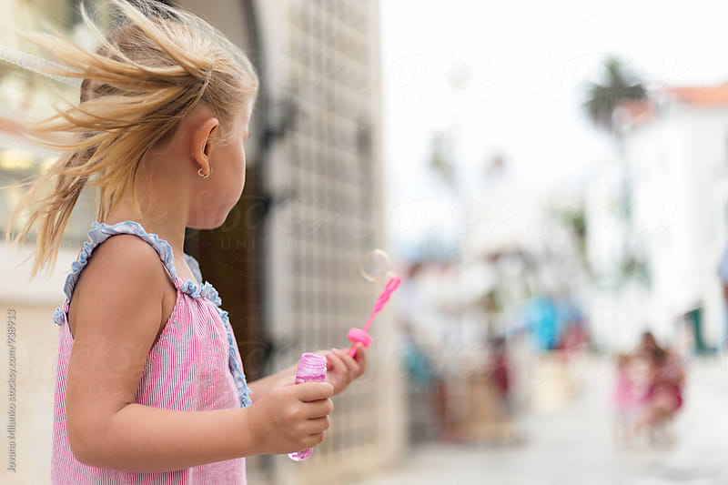 Beautiful little girl standing in the city street allowing wind to make soap bubbles by Jovana Milanko for Stocksy United