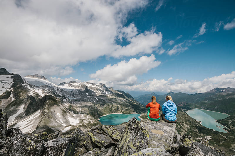 two female hiking friends with colorful outfit sitting in high alpine scenery with a panorama view by Leander Nardin for Stocksy United