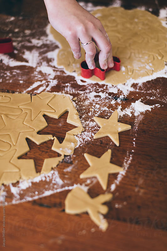 Girls hands cutting Christmas shapes out of gingerbread biscuit dough by Jacqui Miller for Stocksy United