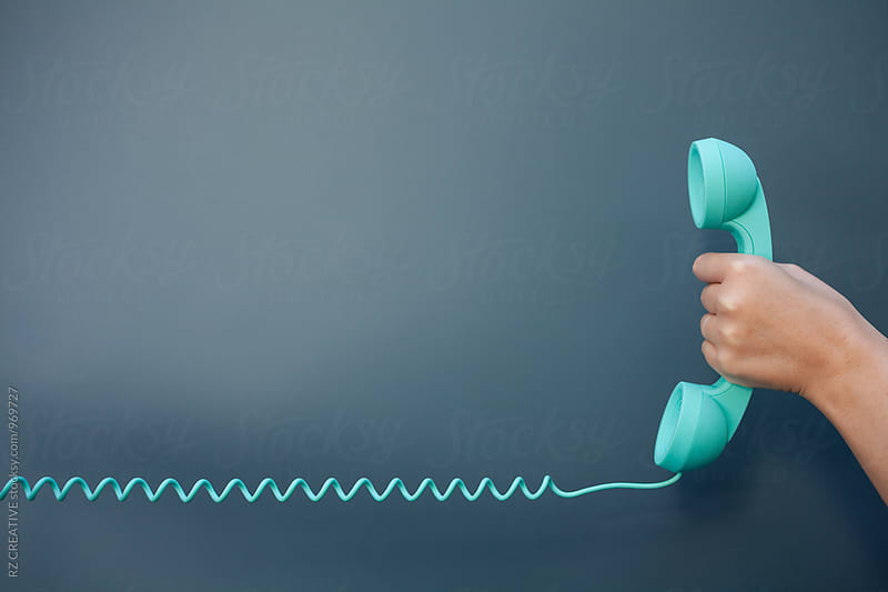 Hand holding up telephone. by RZ CREATIVE for Stocksy United