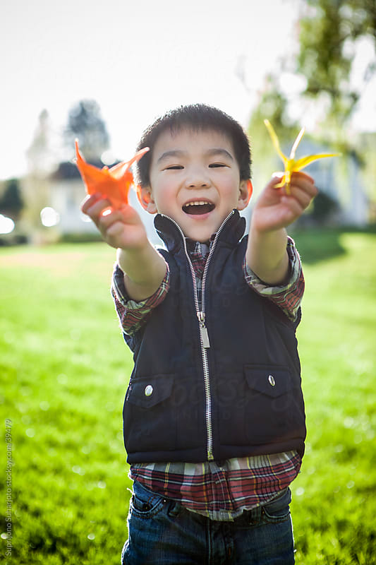 Happy Asian boy showing his paper craft/origami toy by Suprijono Suharjoto for Stocksy United