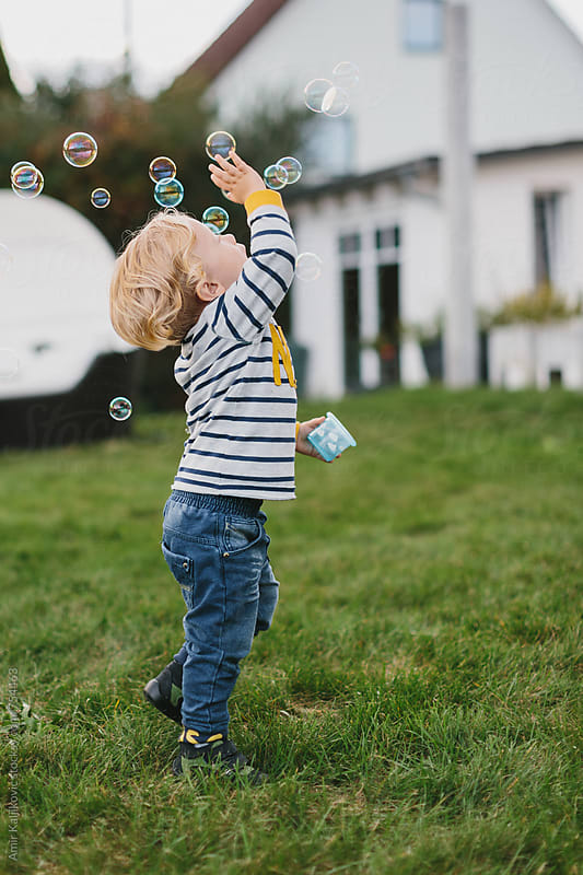 Young boy playing with bubbles by Amir Kaljikovic for Stocksy United