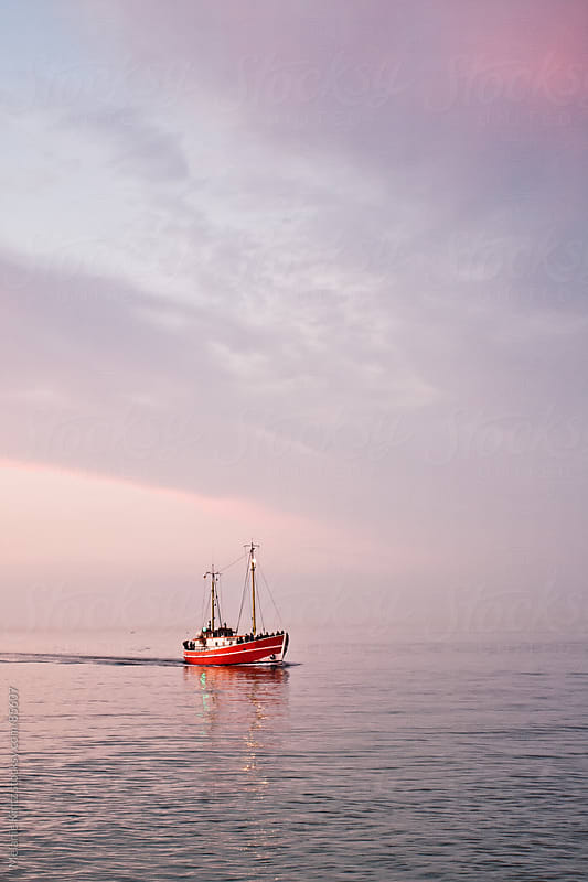 Fishing boat coming home at sunset, minimalist composition by Melanie Kintz for Stocksy United