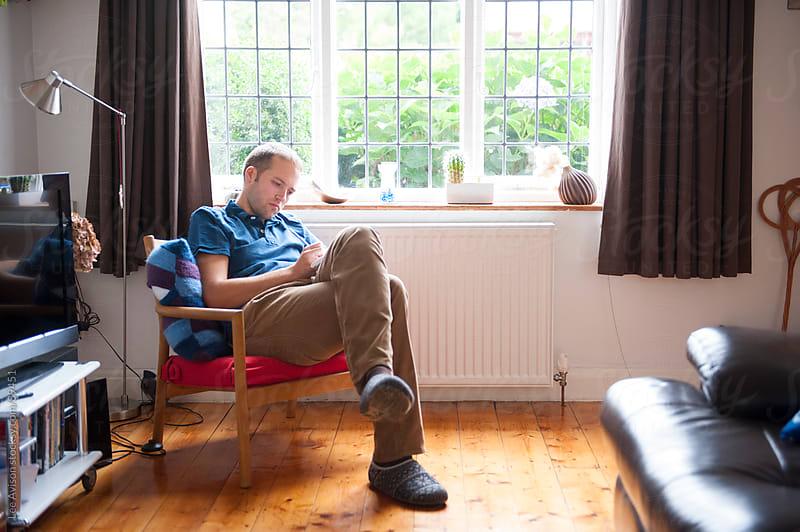 caucasian man by a window by Lee Avison for Stocksy United