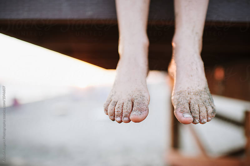 Child's feet hanging off lifeguard stand with sandy feet by Kristin Rogers Photography for Stocksy United
