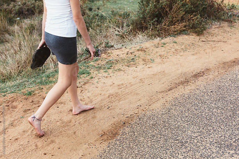 Legs of teenage girl, wearing a short skirt, walking barefoot along a road by Jacqui Miller for Stocksy United