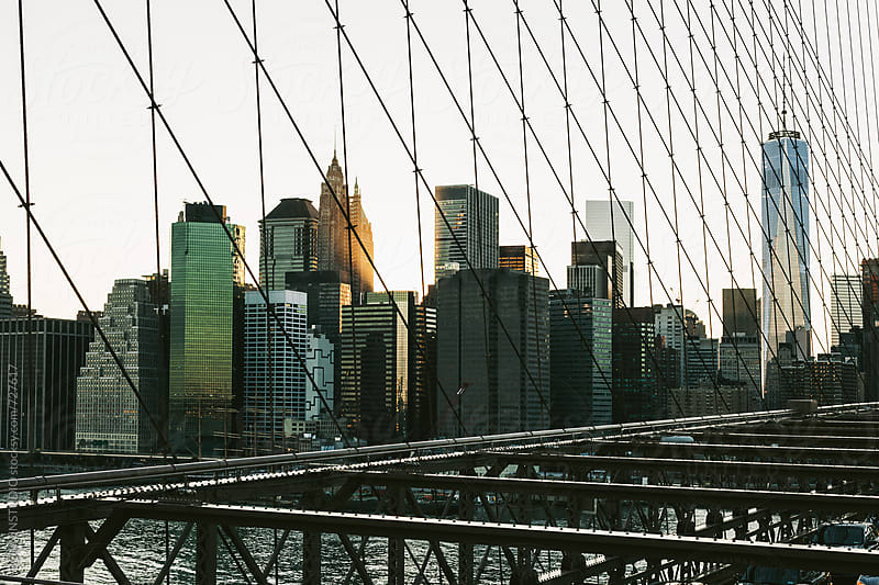 Views of Manhattan from Brooklyn bridge at sunset. by BONNINSTUDIO for Stocksy United