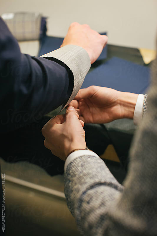 Men's Fashion - Close Up of Male Tailor Showing Suit Fabric to Customer by VISUALSPECTRUM for Stocksy United