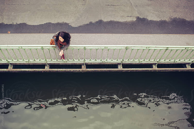 A woman resting on the bridge, watching the river. by michela ravasio for Stocksy United