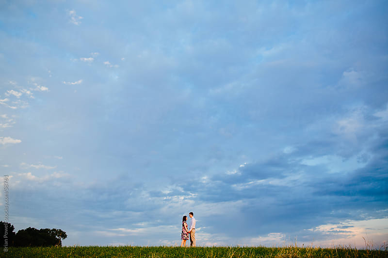 couple together under blue sky by Brian Powell for Stocksy United