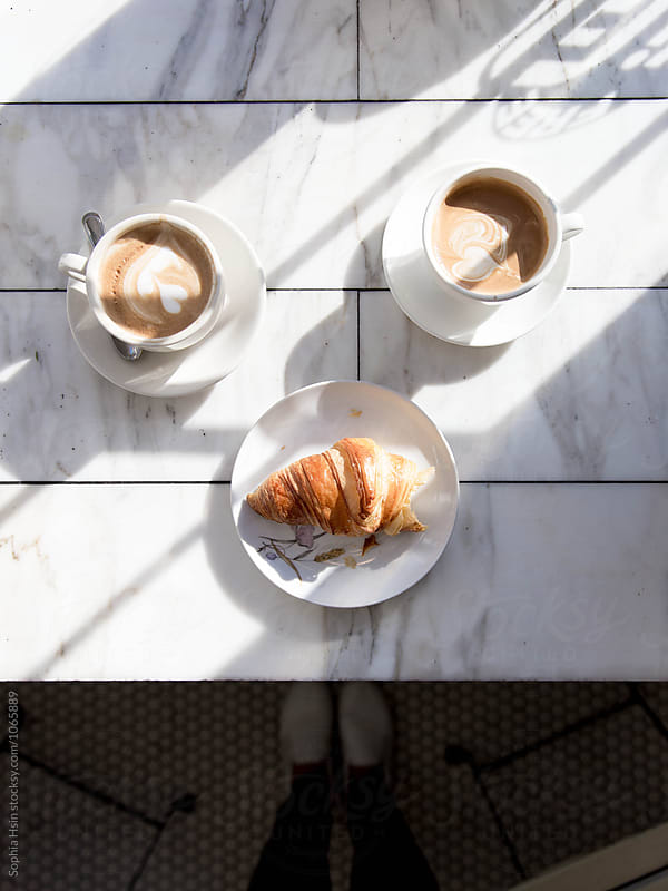 Coffee and croissants with light and shadows by Sophia Hsin for Stocksy United