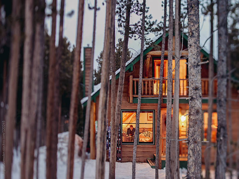 Snow covered cabin in a mountain forest in the evening by Angela Lumsden for Stocksy United