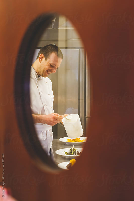 Chef Finishing the Dishes in the Kitchen of a Traditional Italian Restaurant by Giorgio Magini for Stocksy United