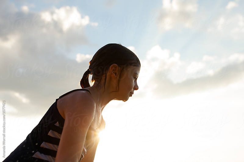 Profile of girl in bathing suit with summer sun setting behind her by Amanda Worrall for Stocksy United