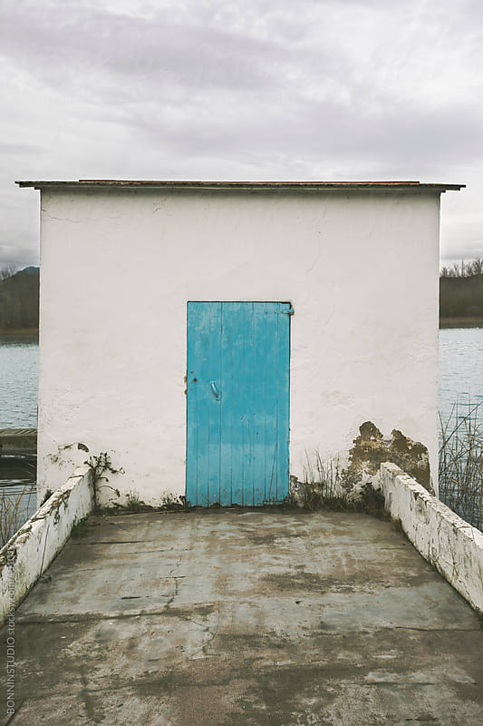 Typical floating house with blue door at Banyoles Lake, Spain by BONNINSTUDIO for Stocksy United