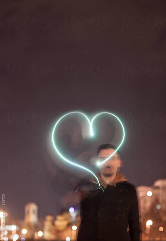 Man Drawing Light Heart in the Air  by Mosuno for Stocksy United