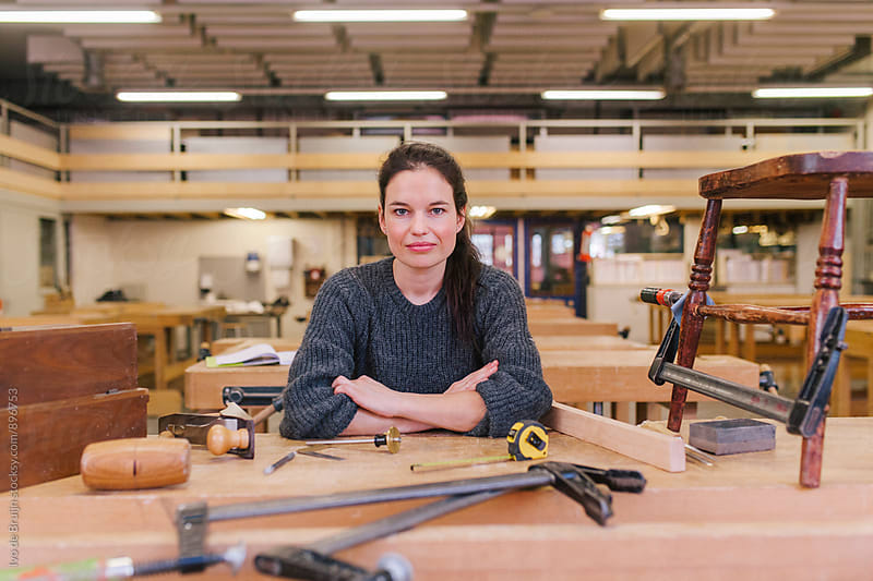 Female woodworker working on a bench, looking at the camera by Ivo de Bruijn for Stocksy United