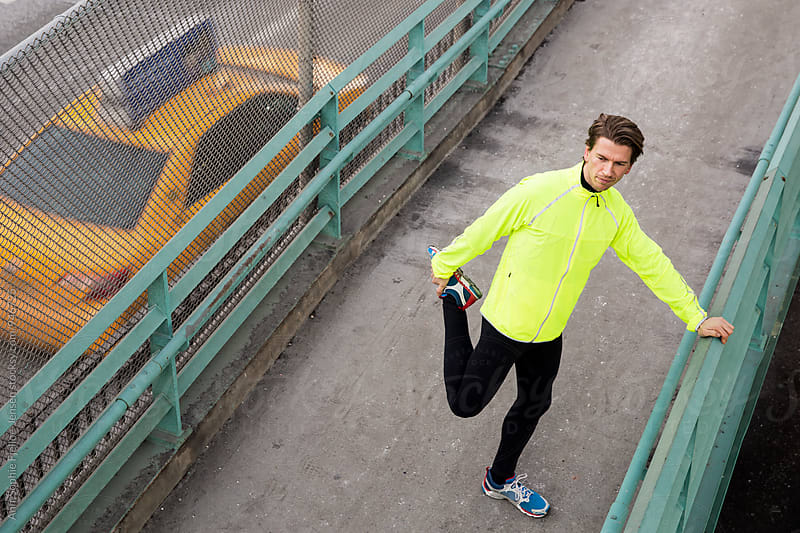 Male runner stretching by the FDR in NYC by Ann-Sophie Fjelloe-Jensen for Stocksy United
