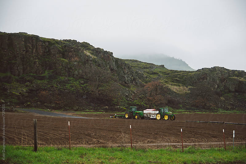 Tractors sitting in field by a foggy hillside by Kate Daigneault for Stocksy United