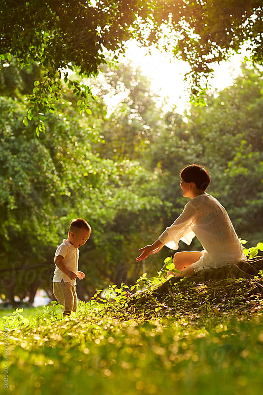 young asian mother with her son under the tree at the sunny park by Bo Bo for Stocksy United