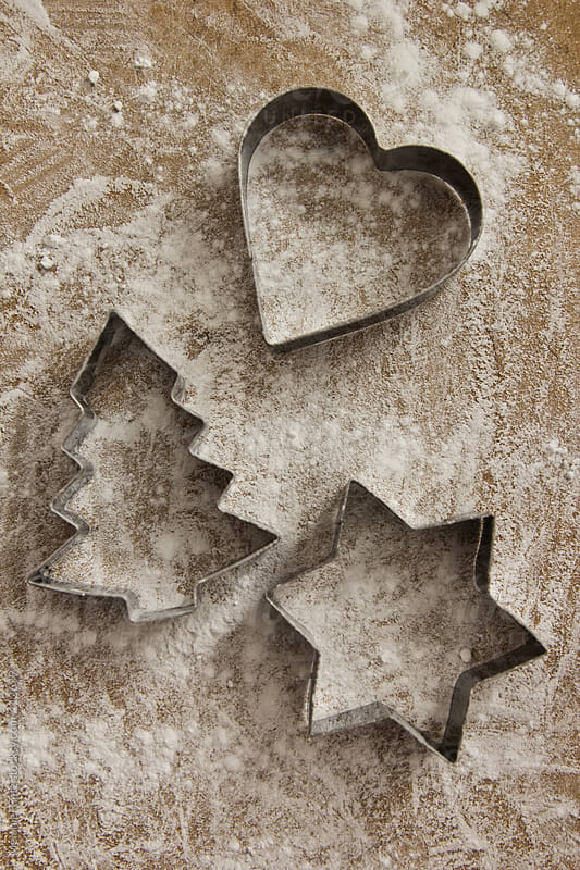Star, heart and christmas tree shaped cookie cutters on wooden board covered with flour by Melanie Kintz for Stocksy United