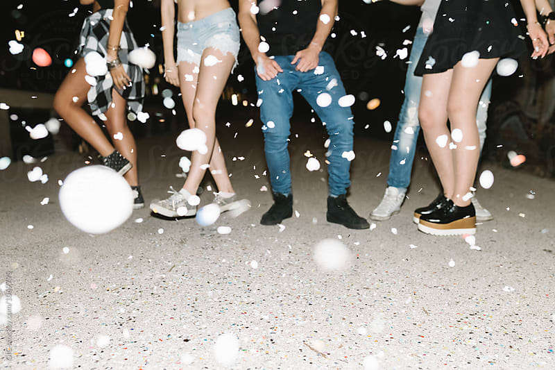 Friends dancing under a confetti rain during a night party by Simone Becchetti for Stocksy United